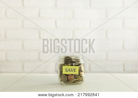 Yellow Save Tag On Saving Money Container That Full Of World Coins White Bricks On Background. Save
