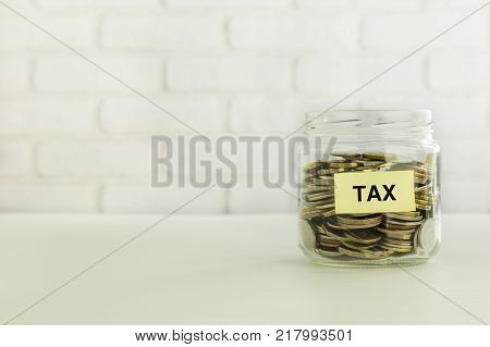 Yellow Tax Label On Saving Glass Jar With World Coins White Bricks Background. Tax Strategies To Sav