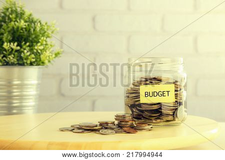 Coins in money jar and on wooden table with yellow BUDGET tag bricks and plant pot on background vintage retro style. Financial management and saving plan for future goal or business marketing concept.