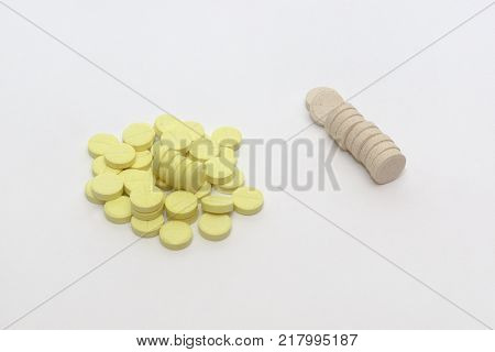 handful of yellow tablets with parting lines and neat stack of beige pills
