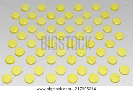 many yellow pills are arranged by chequerwise