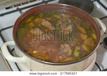delicious meat soup boiling on the stove. The famous Caucasian dishes
