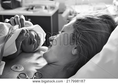 The first moments of mother and newborn after childbirth. Mother holding her newborn baby child after labor in a hospital.