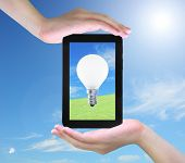 light bulb on tablet PC in women hand poster