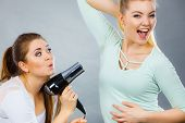 Woman using dryer drying her friend wet armpit having fun together. Sweating problem concept. poster
