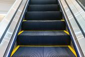 Escalator in Community Mall Shopping Center. Moving up staircase. electric escalator. Close up to escalators. Close up floor platform. yellow bands. metal line steel. yellow gray steel line. poster