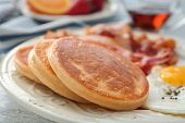 Plate with yummy pancakes, fried bacon and egg on table, closeup poster