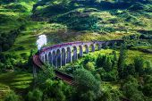 Glenfinnan Railway Viaduct in Scotland with the Jacobite steam train passing over. Artistic vintage style processing. poster