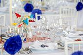 Circle dinner table served with white crockery and decorated with colorful objects. poster