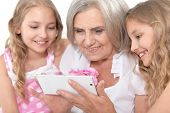 Portrait of granny with her granddaughters using smartphone poster