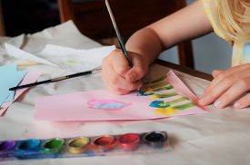 Child painting a picture. A little girl's hand holding a paintbrush as she paints flowers on pink paper. Arts and crafts concept. Traditional play concept.