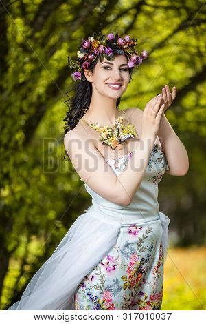 Fantastic Portrait Positive Sensual Brunette Female in White Dress Outdoors. Posing with Flowery Chaplet and Butterfly Against Sunlight.Vertical Image Composition poster