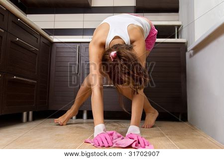 Young woman cleaning the kitchen floor at home