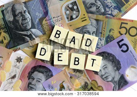 Bad Debt Signage On A Bed Of Australian Dollars.