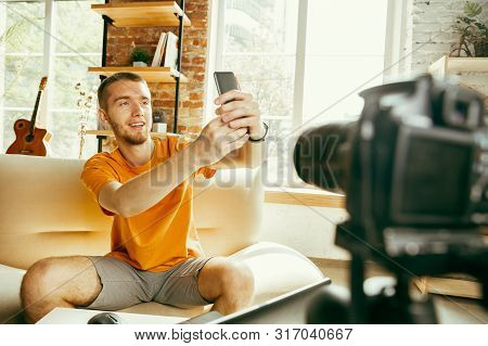 Young Caucasian Male Blogger With Professional Camera Recording Video Review Of Smartphone At Home.
