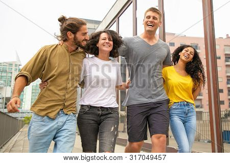 Team Of Joyful Carefree Friends Having Fun Together Outside. Young Men And Women Walking In City, Hu