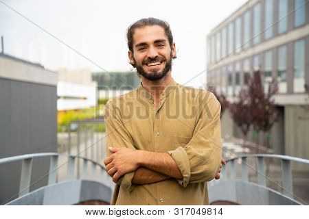 Happy Joyful Hipster Guy Posing For Camera Outside. Young Man In Casual With Bun And Stubble Standin