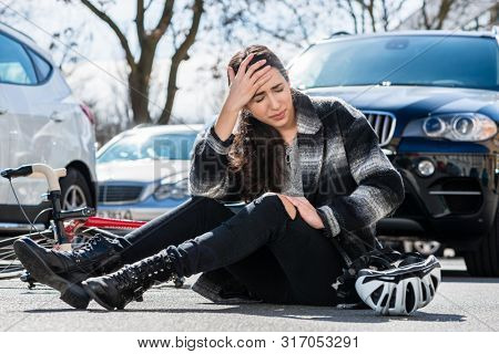 Full length of a young woman sitting on the asphalt with severe headache and dizziness after bicycle accident on a busy city street