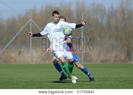 KAPOSVAR, HUNGARY - MARCH 17: Richard Csaki (in white) in action at the Hungarian National Championship under 18 game between Kaposvar(white)  and Videoton (blue) March 17, 2012 in Kaposvar, Hungary.