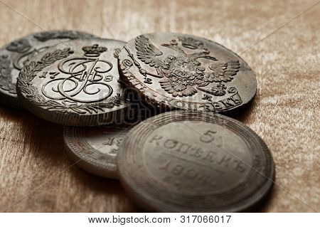 Numismatics. Old Collectible Coins Made Of Copper On A Old Wooden Table. Background.