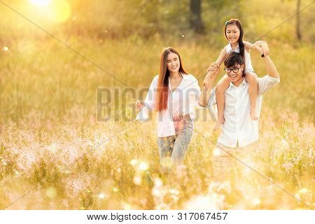 Asian Family Father, Mother And Daughter Play Togather In The Outdoor Park With Sunrise And Goldent