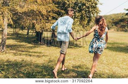 Rear View Of Romantic Couple In Love Dating Outdoors At The Park On A Sunny Day. Happy Couple In Lov