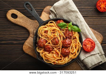 Top View Of Delicious Pasta With Meatballs, Tomato Sauce And Fresh Basil In Cast Iron Rustic Vintage