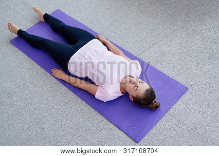 Young Woman Lying On Yoga Mat With Eyes Closed In Savasana Pose At Home. Fitness, Sport And Healthy