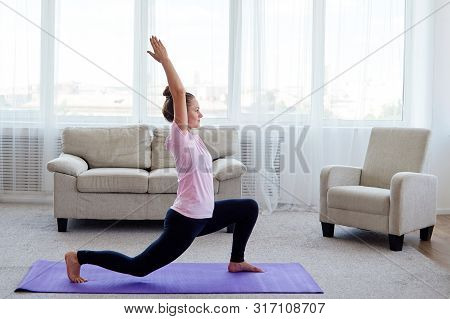 Portrait Of Young Yogini Woman Practicing Balance Yoga Asana Virabhadrasana At Home, Copy Space. Rel