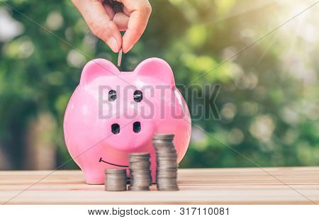 poster of Hand putting a coin into piggy bank. planning savings money of coins to buy a home concept concept for property ladder, mortgage and real estate investment. for saving or invest for a house,