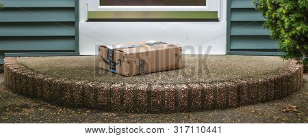 Babylon, New York, Usa - 13 June 2019: A Package Is Delivered And Left On A Front Porch Wet From The