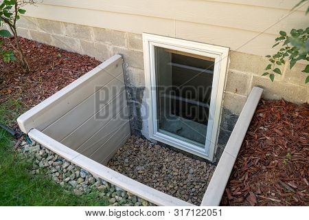 Exterior View Of An Egress Window In A Basement Bedroom. These Windows Are Required As Part Of The U