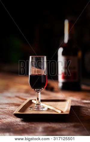 Glass Of Port Wine On Wooden Table And Over Dark Background
