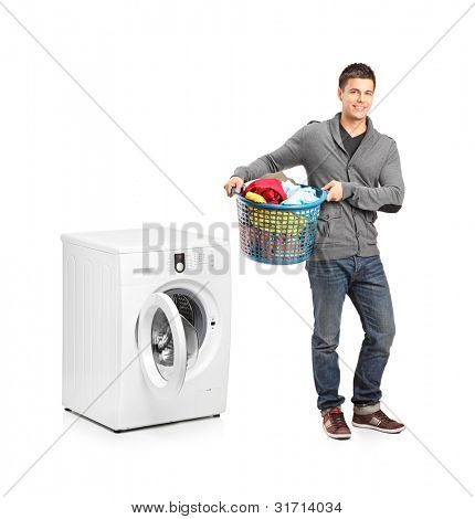 Full length portrait of a man with laundry basket posing next to a washing machine isolated on white background
