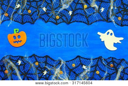 Halloween border. Halloween background with spider web, spiders and smiling jack and ghosts decorations as symbols of Halloween on the dark blue wooden background. Halloween concept