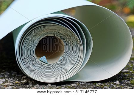 One Roll Of Blue White Paper Lies On Gray Asphalt On The Street