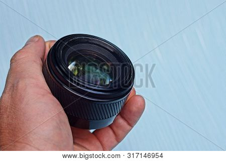 One Black Camera Lens In A Hand On A Blue Background