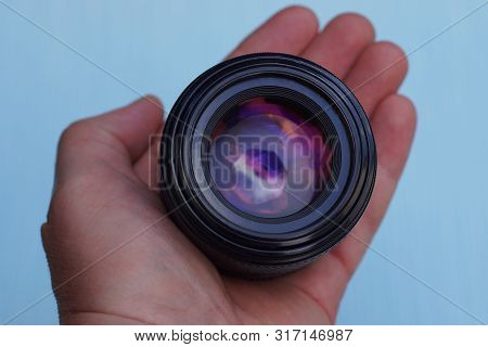 Black Open Camera Lens In A Hand On A Blue Background