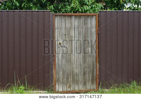 Gray Wooden Door And Brown Metal Fence On The Street In Green Grass
