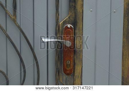 Old Rusty Door Handle On A Gray Metal Door