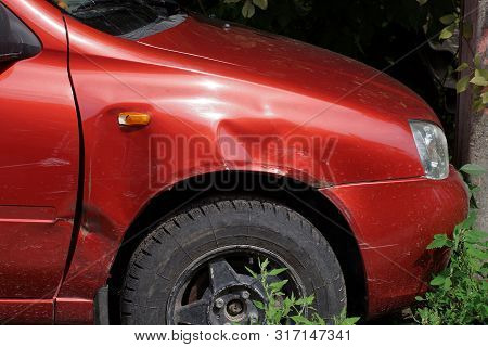 Part Of A Red Car With Rumpled Metal And A Black Wheel In Green Grass