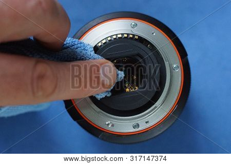 Fingers Hold A Blue Cloth Napkin And Clean The Glass On The Lens Of The Camera