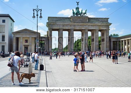 BERLIN, GERMANY - MAY 24, 2018: Locals and tourists at the Pariser Platz square in front of the popular Brandenburg Gate in Berlin, one of the main landmarks in the city