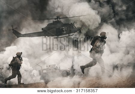 Military Helicopter And Forces Between Fire And Dust In The Battlefield At Sunset / Focus On Helicop