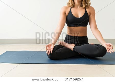 Low Section Of Female Meditating While Practicing Padmasana On Mat Against Wall