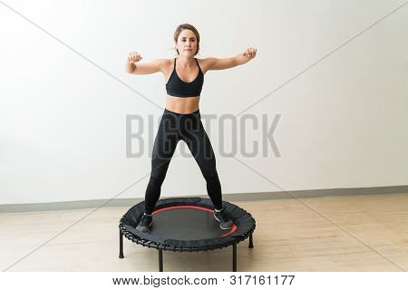Attractive Young Woman In Sportswear Jumping On Mini Trampoline Against White Wall During High Inten