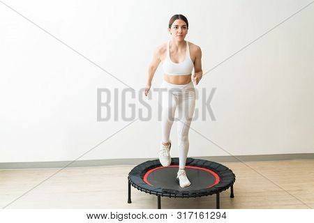 Dedicated Young Woman In White Sportswear Trampolining Against Wall During High Intensity Interval T
