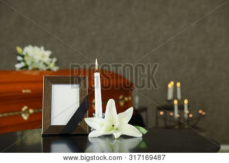 Black Photo Frame With Burning Candle And White Lily On Table In Funeral Home