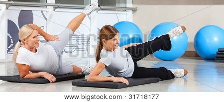 Two elderly women exercising together in fitness center on gym mats