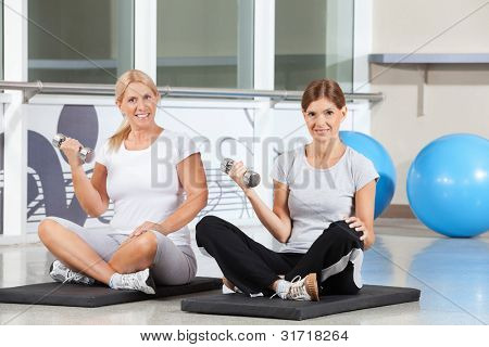 Two happy women doing dumbbell exercises on gym mats in fitness center